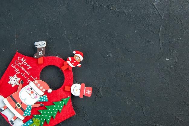 Clima natalino com acessórios de decoração e caixa de presente de ano novo no lado direito em superfície escura