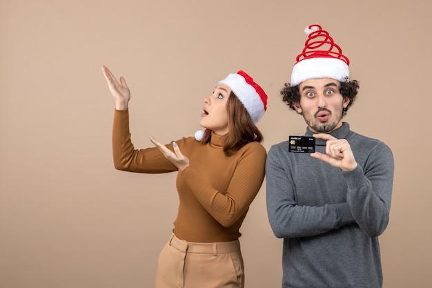 Clima natalino com animado, satisfeito, chocado, casal legal usando chapéu de papai noel vermelho mostrando cartão do banco