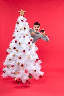 Clima natalino com cara emocional atrás da árvore de natal decorada e pegando o telefone