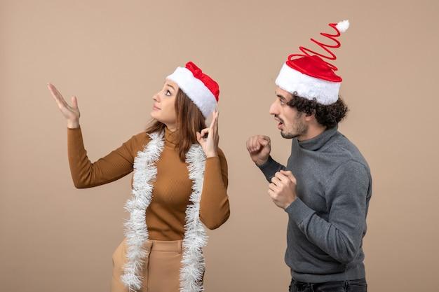 Clima natalino com casal animado e satisfeito com chapéu de papai noel vermelho apontando para cima