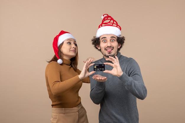 Clima natalino com casal animado e satisfeito com chapéu de papai noel vermelho mostrando cartão do banco