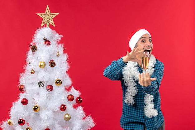 Clima natalino com jovem feliz com chapéu de papai noel em uma camisa azul listrada levantando uma taça de vinho perto da árvore de natal