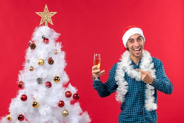 Clima natalino com jovem feliz com chapéu de papai noel em uma camisa azul listrada segurando uma taça de vinho perto da árvore de natal