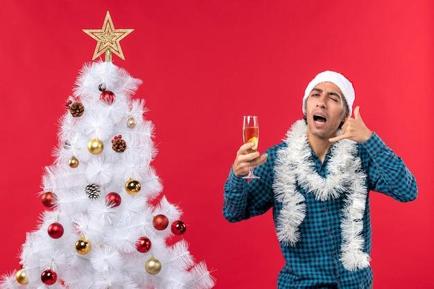 Clima natalino emocional jovem com chapéu de papai noel em uma camisa azul listrada segurando uma taça de vinho e fazendo um gesto de me ligar perto da árvore de natal