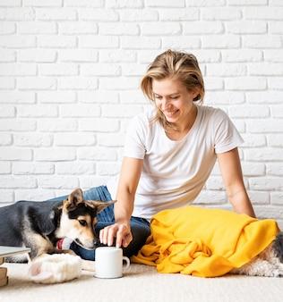 Clínica de cuidado de animais domésticos. mulher jovem engraçada em xadrez amarelo sentada no chão brincando com seus cachorros