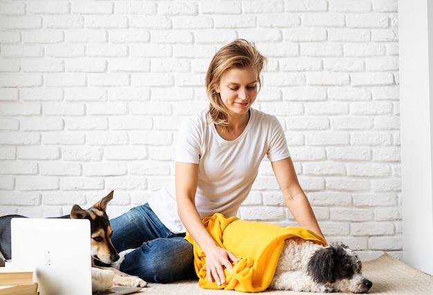Clínica de cuidado de animais domésticos. mulher jovem engraçada em xadrez amarelo sentada no chão com seus cachorros