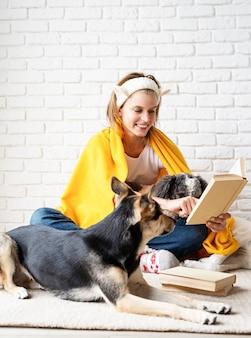 Clínica de cuidado de animais domésticos. mulher jovem sorridente e engraçada em xadrez amarelo sentada com seus cachorros lendo um livro