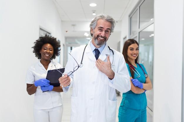 Clínica, profissão, pessoas, cuidados de saúde e conceito de medicina feliz grupo de médicos ou médicos no corredor do hospital.