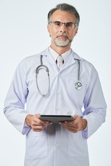 Clínico geral com estetoscópio sobre os ombros, segurando a guia digital e olhando para a câmera