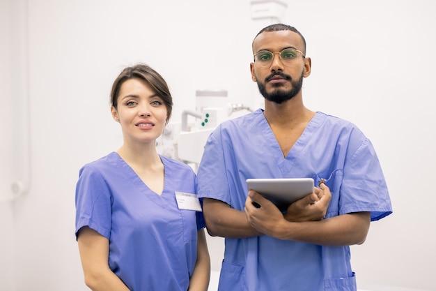 Clínicos interculturais bem-sucedidos ou estagiários uniformizados em pé na frente da câmera durante o trabalho no hospital