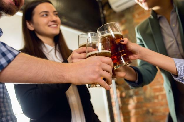Clinking. felizes colegas de trabalho comemorando o evento corporativo após um dia tenso de trabalho. pareça encantado, amigável, alegre. bebendo cerveja. conceito de cultura de escritório, trabalho em equipe, amizade, feriados, fim de semana.
