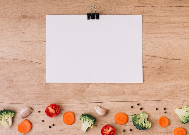 Clipe de buldogue em branco sobre papel branco sobre as fatias de cenoura; tomates cortados ao meio; brócolis; dente de alho e pimenta preta na mesa de madeira