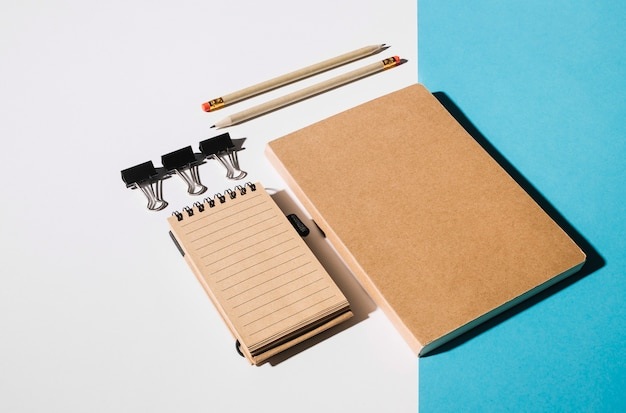 Clipe de buldogue; lápis e livro fechado em fundo duplo