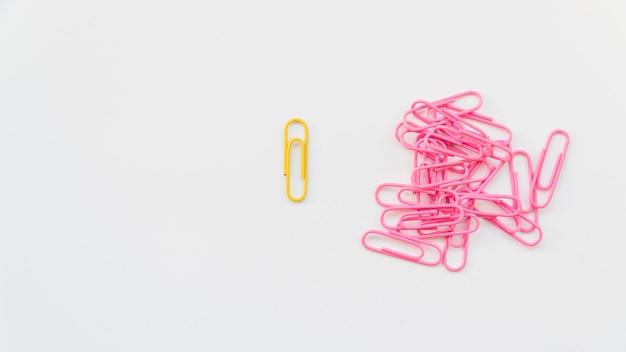 Clipe de papel amarelo separado da pilha de rosa