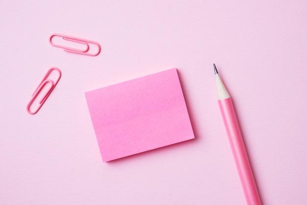 Clipe de papel-de-rosa do bloco de notas e lápis em rosa