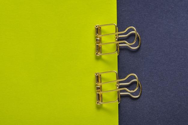 Clipe de papel dourado e folhas de papel em fundo verde e preto