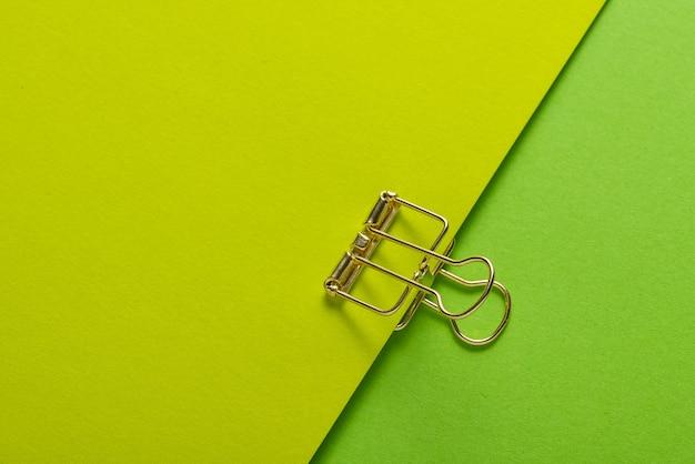 Clipe de papel dourado e folhas de papel em fundo verde
