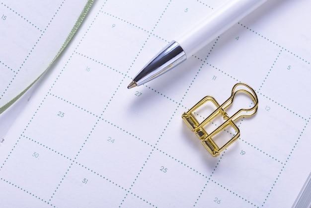 Clipe de papel dourado e lápis no caderno organizador do calendário