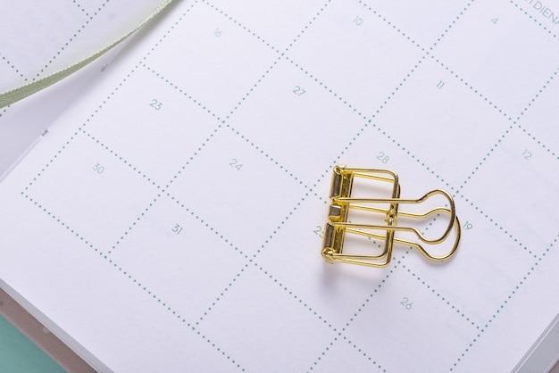 Clipe de papel dourado no caderno organizador do calendário