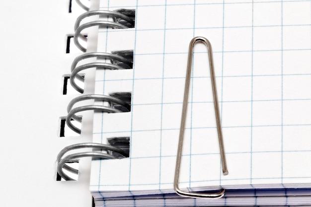 Clipe de papel nas páginas do caderno. isolado sobre o branco.