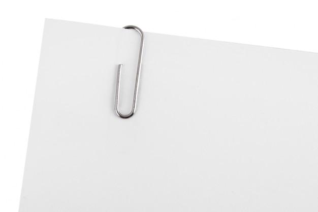 Clipe de papel no canto da nota de papel branco, isolado no branco