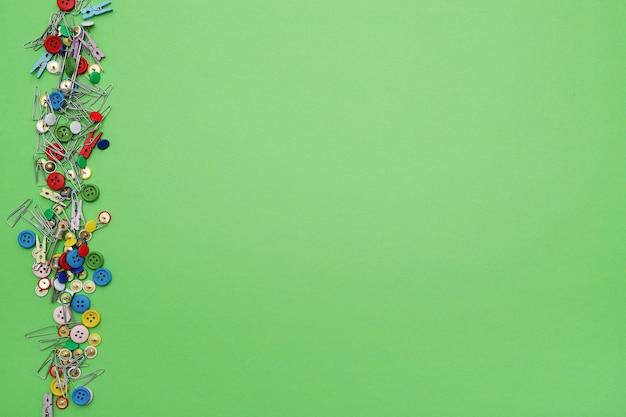 Clipes de costura e botões sobre fundo verde, vista superior