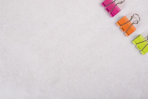 Clipes de papel coloridos em fundo branco.