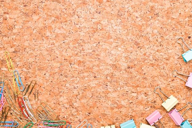 Clipes de papel multicoloridos e clipes de fichário espalhados em fundo de cortiça