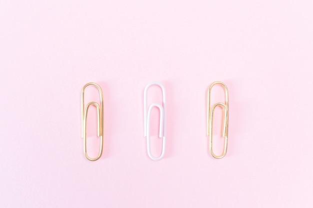 Clipes de papel rosa e dourados sobre um fundo rosa pastel.