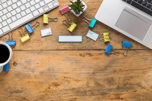 Clipes de papel; teclado; laptop e rótulos na mesa de madeira