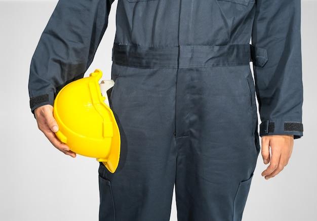 Cloes up trabalhador em pé com macacão azul segurando um capacete amarelo isolado em um fundo cinza