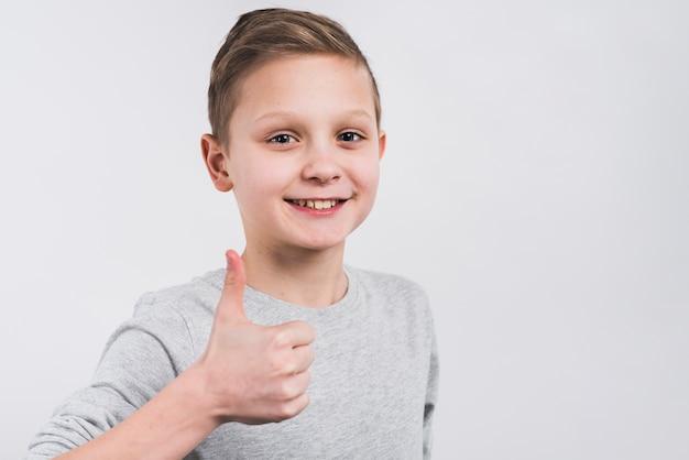 Clos-up de um menino sorridente, mostrando o polegar para cima sinal de pé contra um fundo cinza