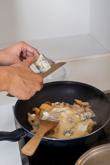Clos-up de uma pessoa cortando o queijo na frigideira
