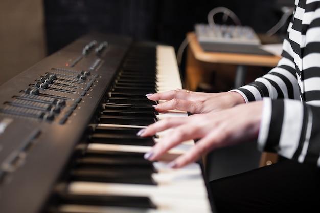 Close com as mãos tocando música de piano