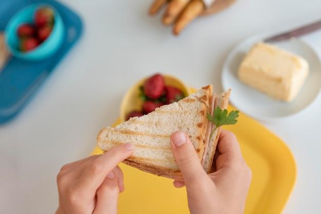 Close criança segurando sanduíche
