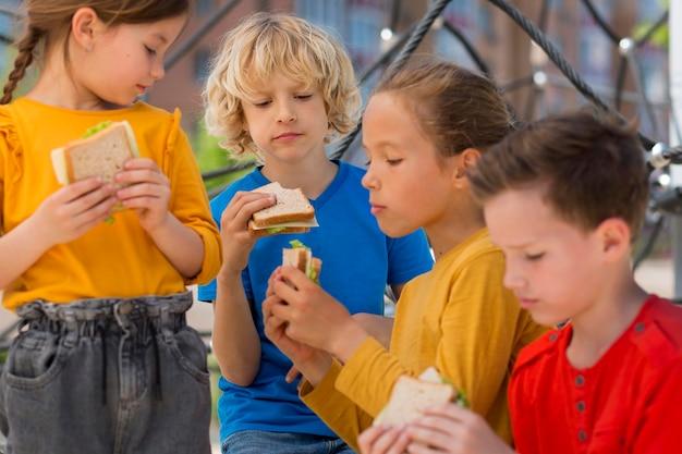 Close, crianças comendo sanduíches