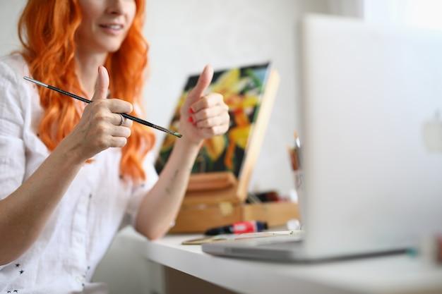 Close da adorável artista feminina mostrando os polegares para cima, olhando no laptop
