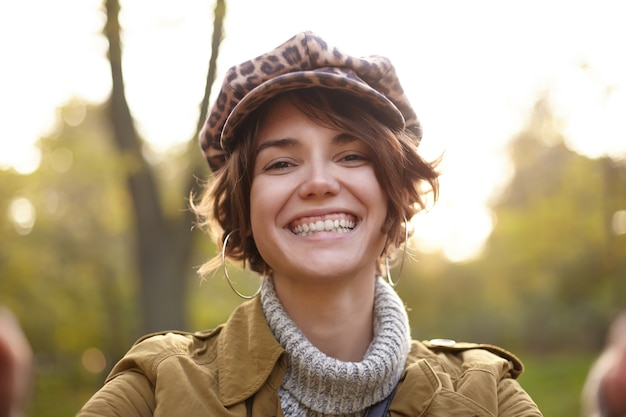 Close da alegre jovem morena de cabelos curtos com maquiagem natural, mostrando seus dentes brancos perfeitos enquanto sorri amplamente, vestida com roupas da moda enquanto posa no jardim da cidade