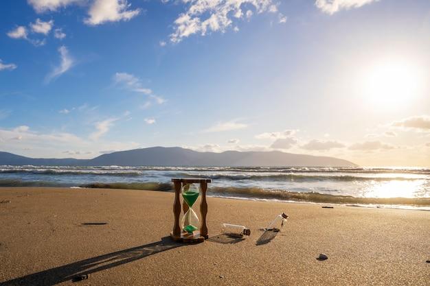 Close da ampulheta no pôr do sol da praia do temporizador de areia