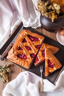 Close da apetitosa torta recheada de frutas vermelhas, típica russa, preparada com um pano branco