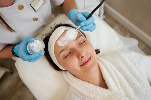 Close da bela mulher sorridente, deitada na mesa de massagem, enquanto a máscara facial é aplicada no rosto.