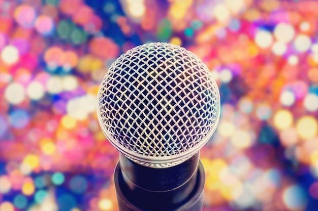 Close da cabeça do microfone em fundo de bokeh colorido