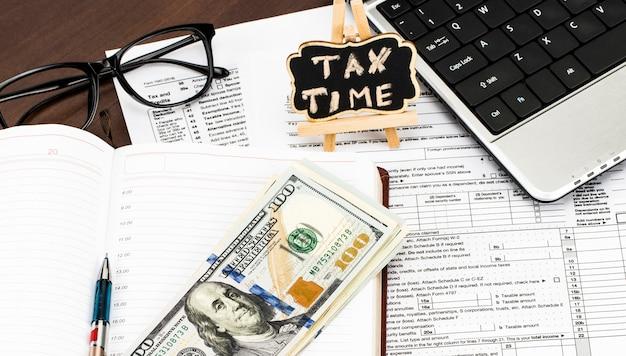 Close da calculadora, formulários fiscais com os óculos, dinheiro e a caneta e o tempo do imposto escrito no quadro-negro.