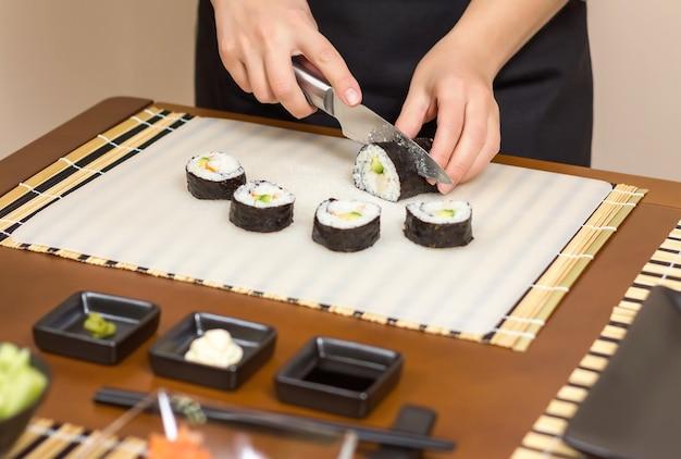 Close da chef mulher cortando rolos de sushi japonês com arroz, abacate e camarão em folha de alga nori