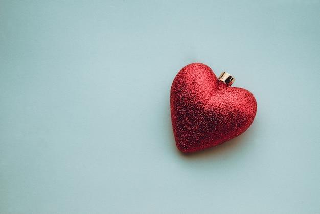 Close da decoração da árvore de natal brilhante em forma de coração em uma superfície azul clara