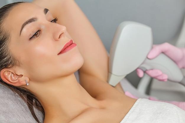 Close da esteticista removendo pelos da axila da mulher