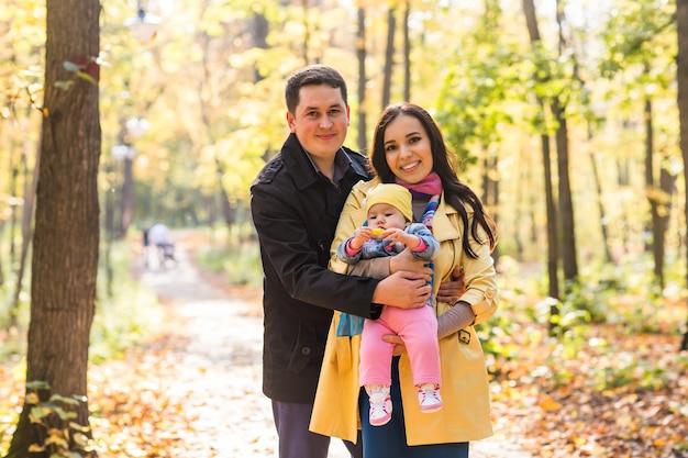 Close da família feliz de mãe, pai e bebê na natureza do outono