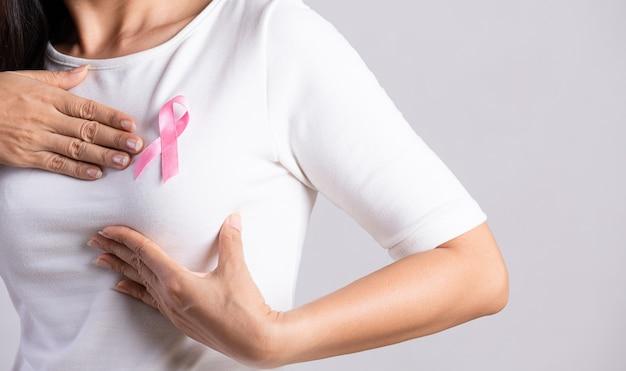 Close da fita rosa do crachá no peito da mulher para apoiar a causa do câncer de mama