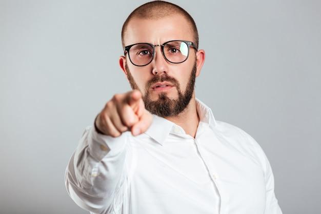 Close da foto de cara determinado de camisa branca e óculos, apontando no dedo indicador da câmera com acusação, isolado sobre a parede cinza