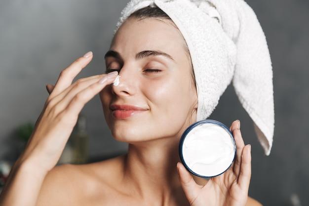 Close da foto de uma mulher alegre enrolada em uma toalha na cabeça, aplicando creme no rosto